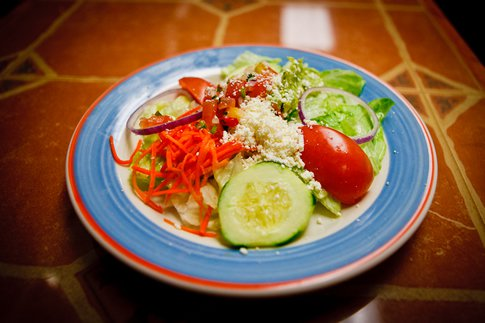 salad in a bowl topped with cucumbers, tomatoes, shredded carrots