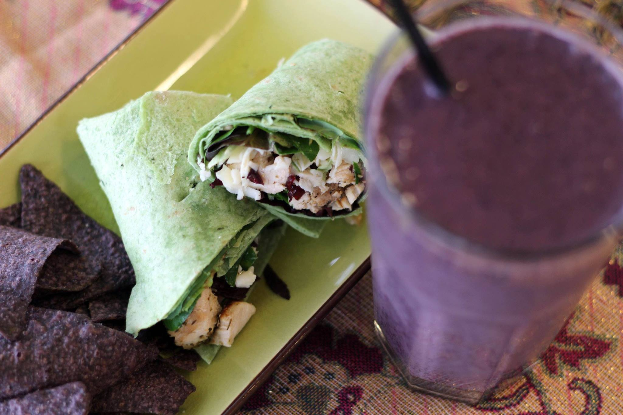 A spinach wrap filled with grilled chicken, cheese and lettuce, next to a smoothie.