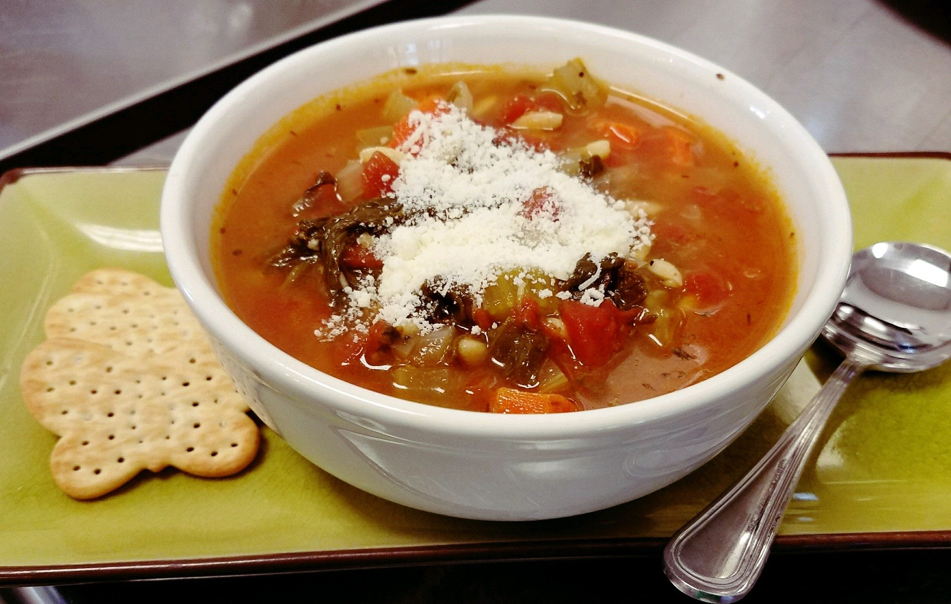 A vegetable soup garnished with cheese. With a side of crackers.