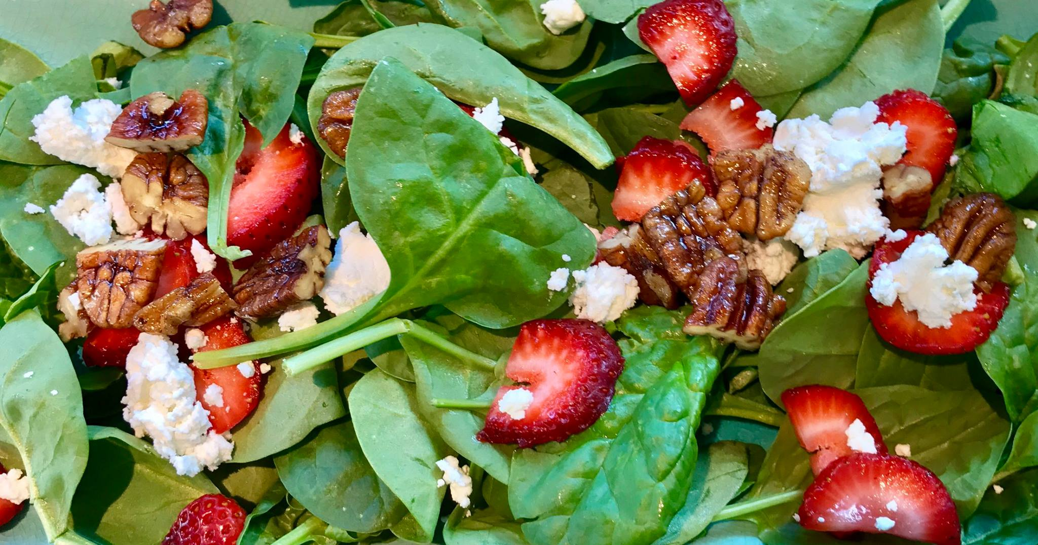 A close up of a spinach salad with strawberries, walnuts, and crumbled cheese