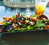 A long plate filled with salad that has a variety of toppings. In the background there is an ice tea with a straw in it.
