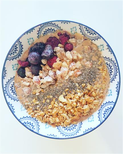 An acai bowl topped with berries and mixed nuts.