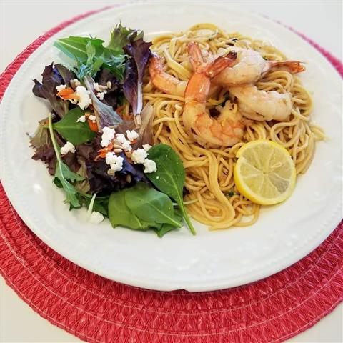 Pasta topped with shrimp and a single piece of lemon served with a side salad.