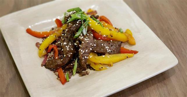 Beef stir fry with peppers over rice topped with a sprinkle of sesame seeds.