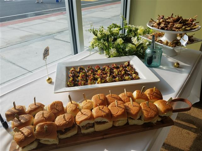 A tray of hamburger sliders next to other platters of food.