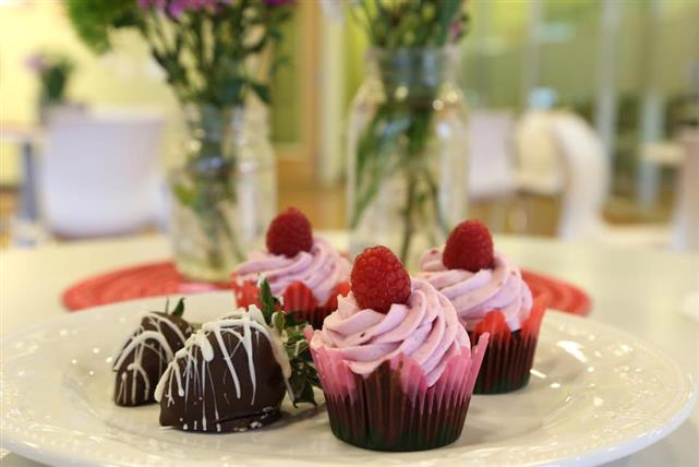 Chocolate cupcakes with pink frosting topped with a single berry, next to chocolate covered strawberries with white chocolate drizzle.