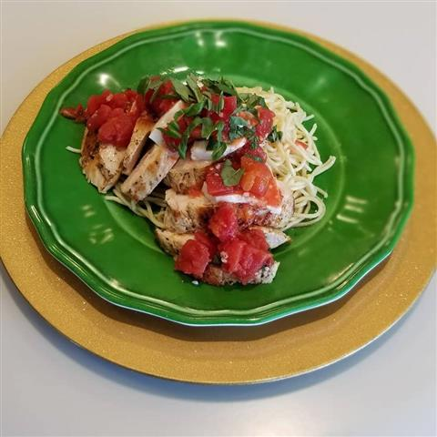 Sliced grilled chicken served with chopped tomatoes over a pasta dish.