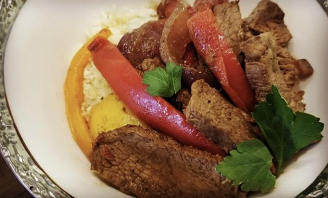 A close up picture of beef tips paired with onions, peppers and rice.