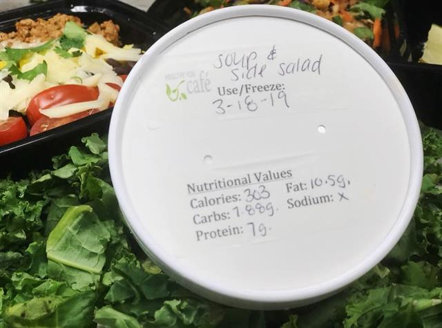 A container of soup with nutrionals listed on it on top of a salad.