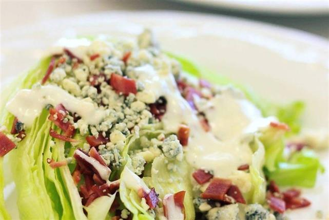 A salad topped with chopped bacon and crumbled bleu cheese with a drizzle of dressing.