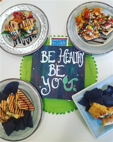 "A sign that says, ""Be healthy be you"" on it, sorrounded by A varity of dishes."