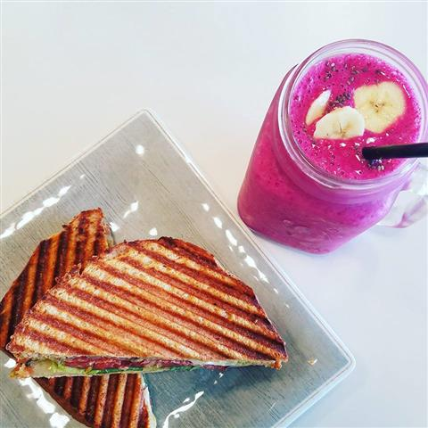 A panini on a plate next to a smoothie topped with bananas on it.