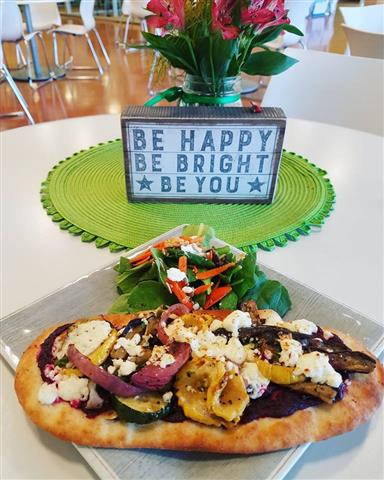 "Naan bread with grilled vegetables on top of it paired with a salad next to a sign that says ""Be happy, Be bright, Be you""."