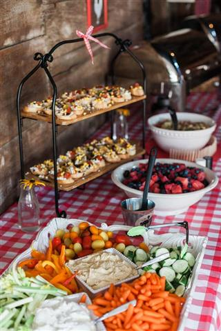 A close up of a food bar with mixed veggies, toast with brushetta topping and a berry salad.