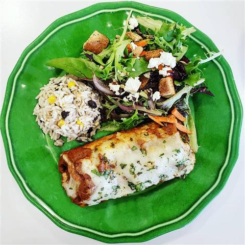 An enchilada paired with rice that contains corn and beans and a salad with crumbled cheese on it.