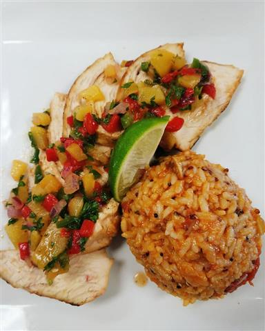 A plate containing grilled chicken topped with a salsa paired with a side of rice.
