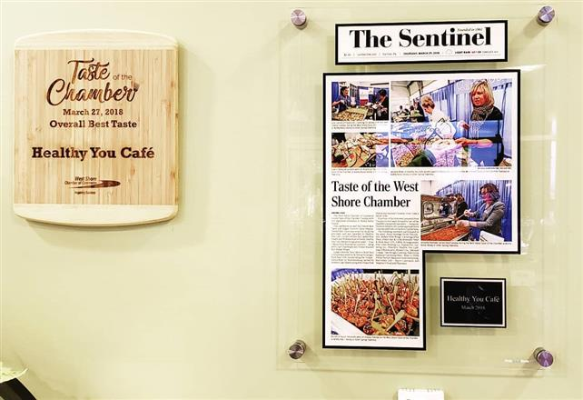 "A wall with a plaque that says ""taste chamber March 27th, 2018"", next to a framed article titled ""Taste of the West Shore Chamber""."