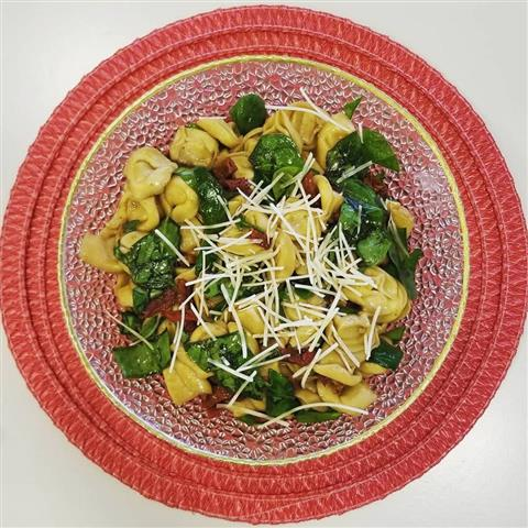 A dish filled with tortellini pasta and spinach topped with cheese.