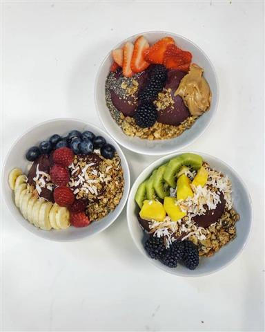 Three different acai bowls topped with a variety of fruits.