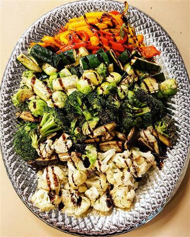 A variety of roasted veggies with a drizzle of sauce on a plate.