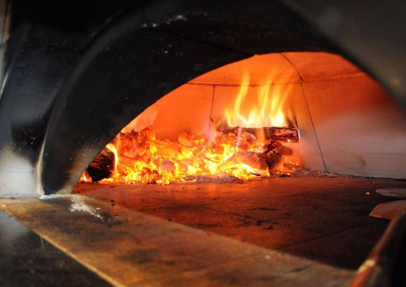 Fire burning wood in a brick oven