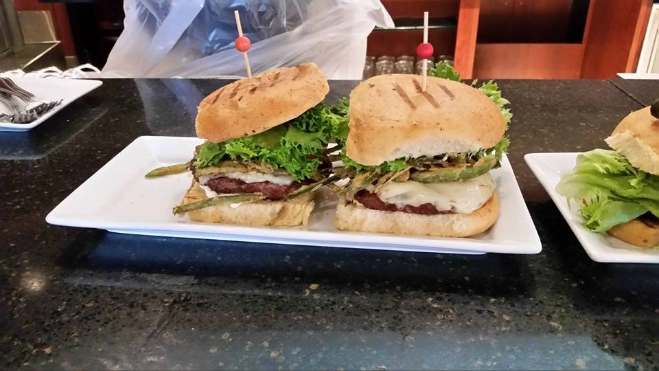 Two half pound burgers with pepperjack cheese, lettuce, on a seedless bun with toothpicks holding the burgers together