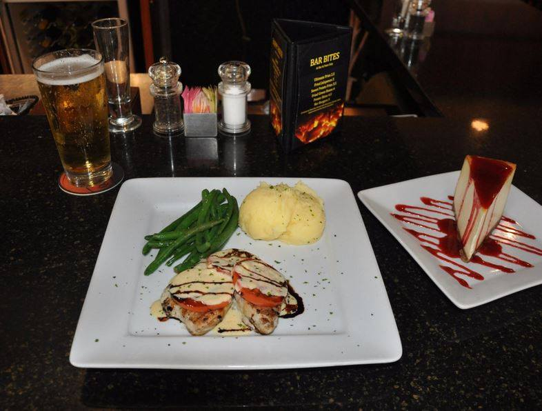 a plate of grilled chicken topped with tomato and mozzarella cheese, with a side of string bean and mashed potatoes. Along side a plate of homemade cheesecake drizzled with strawberry sauce