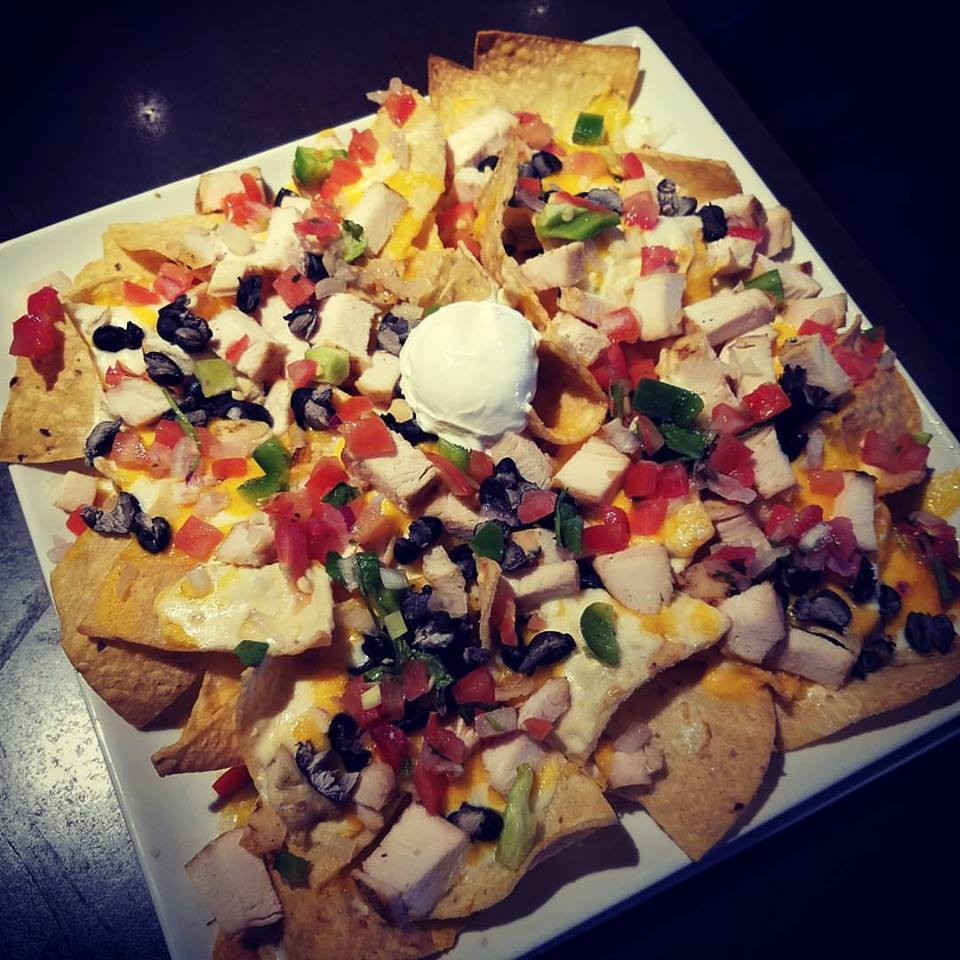 loaded Nachos topped with black beans, cheddar, chicken, and pico de gallo