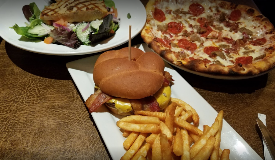 Bacon cheese burger with fries on a white plate surrounded by a pepperoni and sausage pizza, and a fresh garden salad with chicken on top