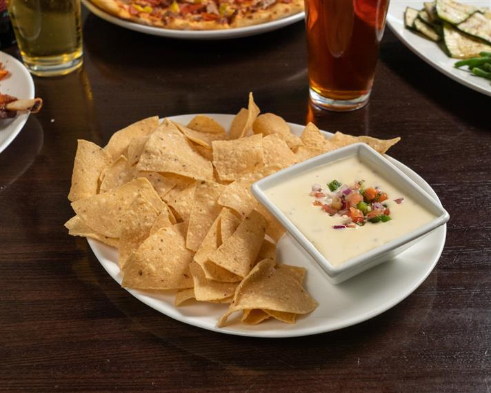 chips and queso on a plate with beer on the side