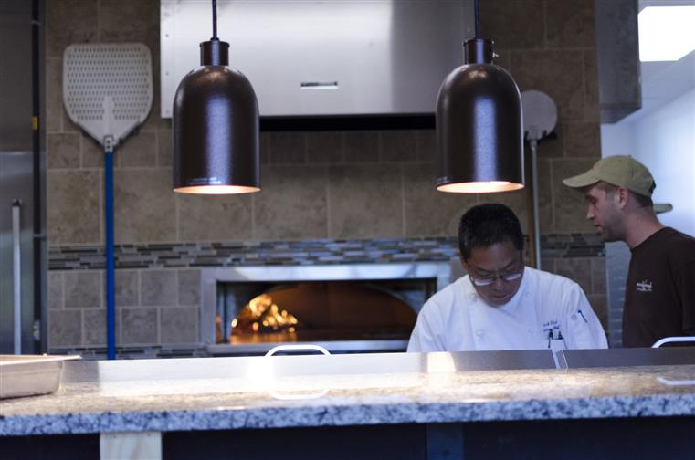 Chef in kitchen behind counter, in front of pizza oven