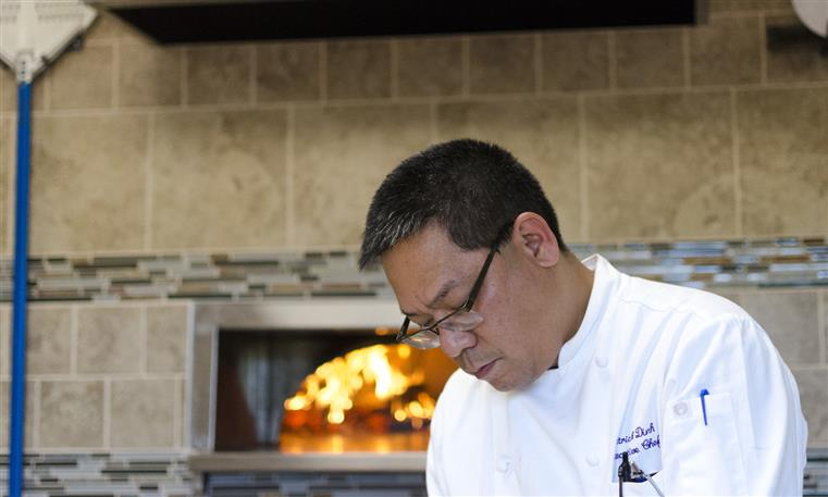 Chef in kitchen in front of pizza oven