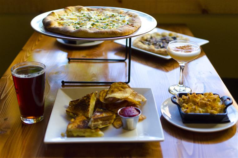 Pizza on serving tray, side of mac and cheese, grilled sandwiches, chips and beer
