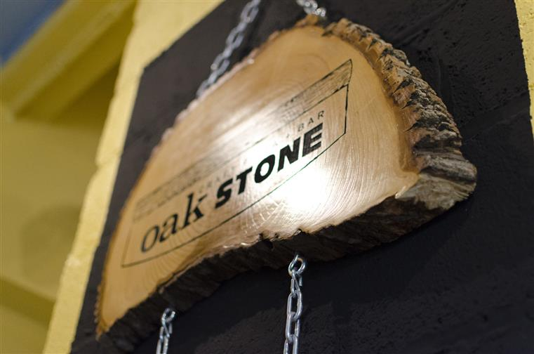 Engraved Oak Stone sign on trunk cross section of oak tree.