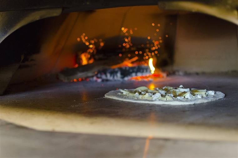 Pizza cooking in wood fired pizza oven