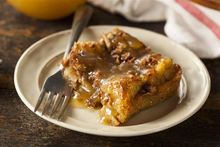 Bread pudding with fork on white dish on wood table