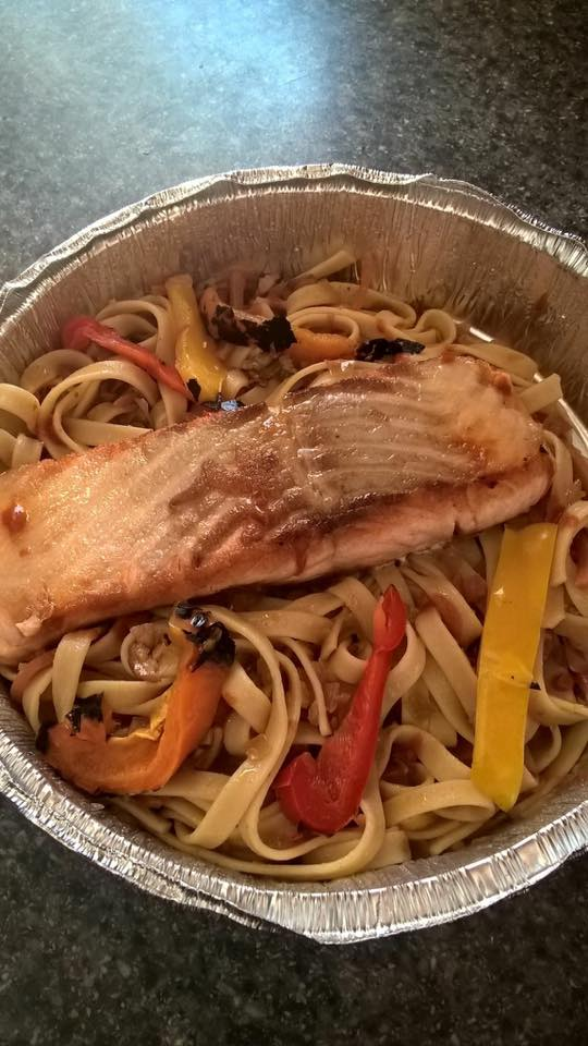 cooked salmon over a bed of pasta