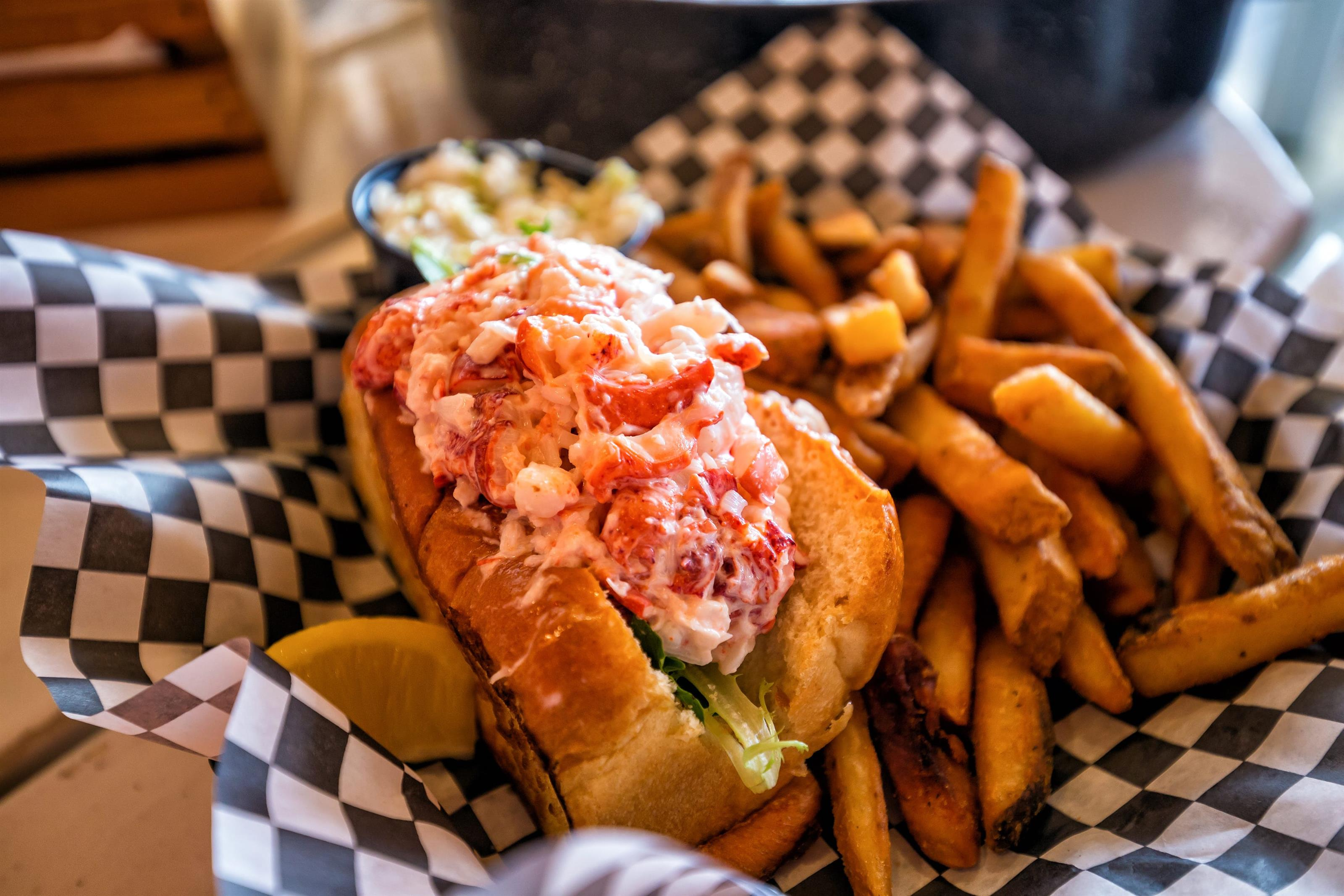 lobster roll in a basket with fries