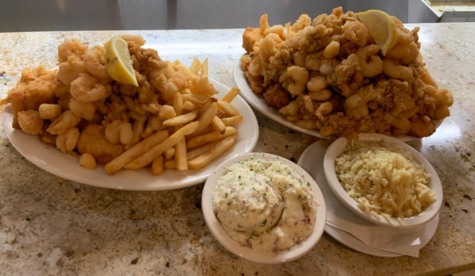 two fried clam dishes with mashed potato and rice sides