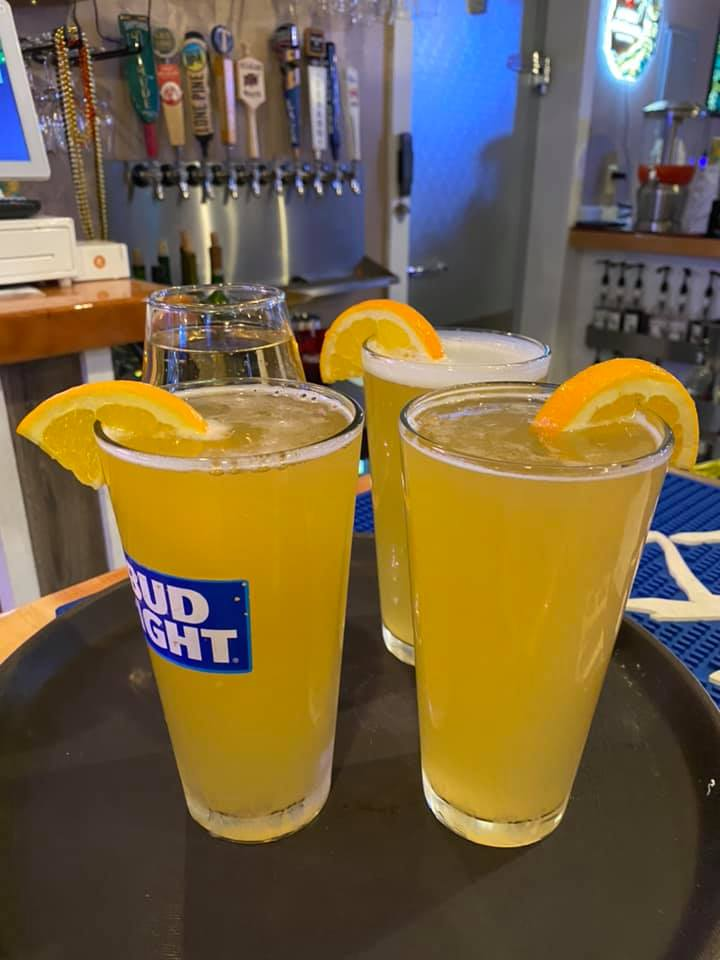 three bud light alcoholic drinks with orange garnish