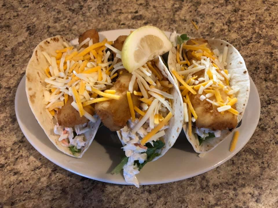 three Fish Tacos with shredded cheese