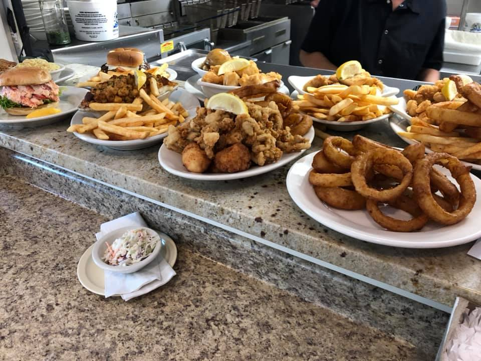 several fried seafood combo platters, with fries, onion rings, coleslaw, and other sides