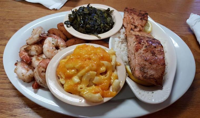 Fish filet and shrimp served with two sides on a tray