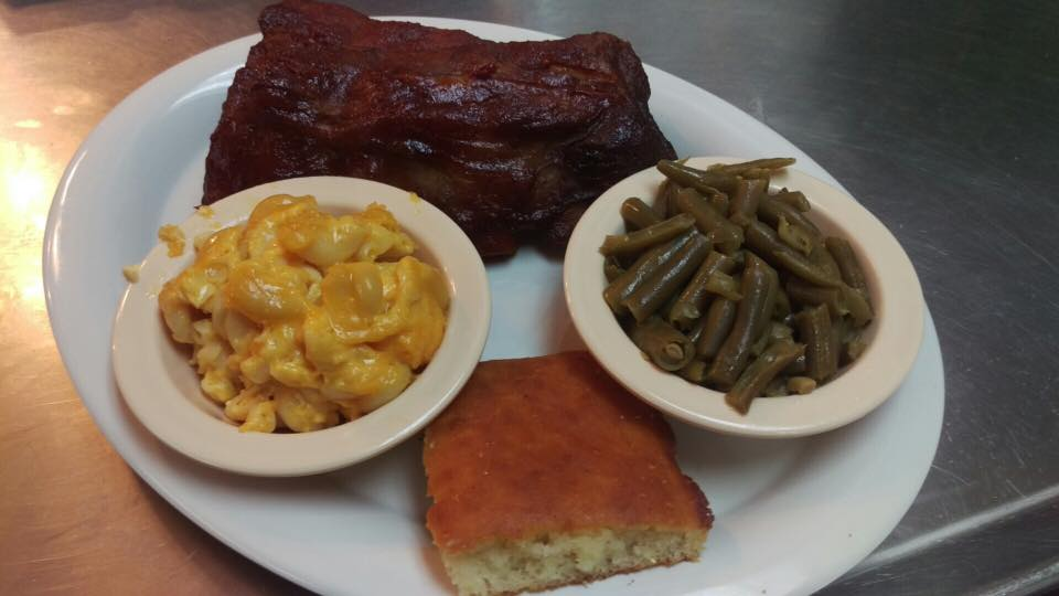 BBQ meat dish served with green beans, mac and cheese and cornbread