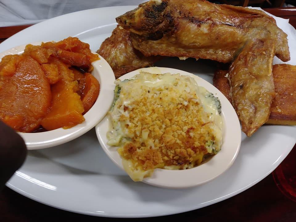 Roasted chicken served with sides of sweet potatoes and mac and cheese