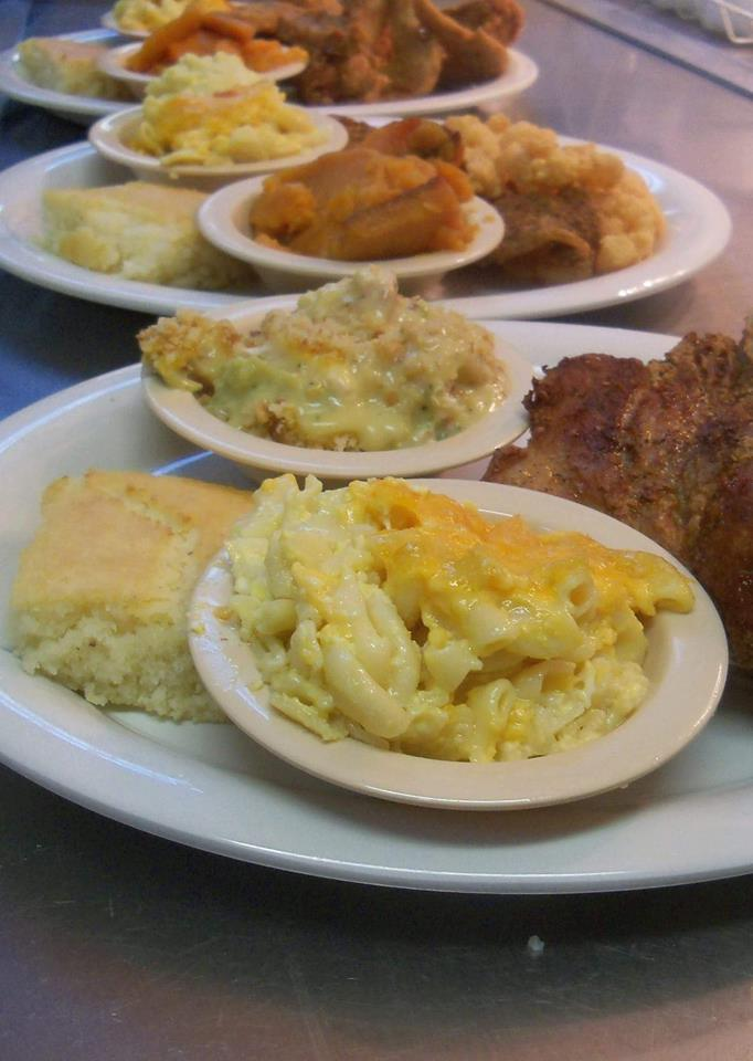 Meat plates served with different side dishes of mac and cheese, greens and other sides