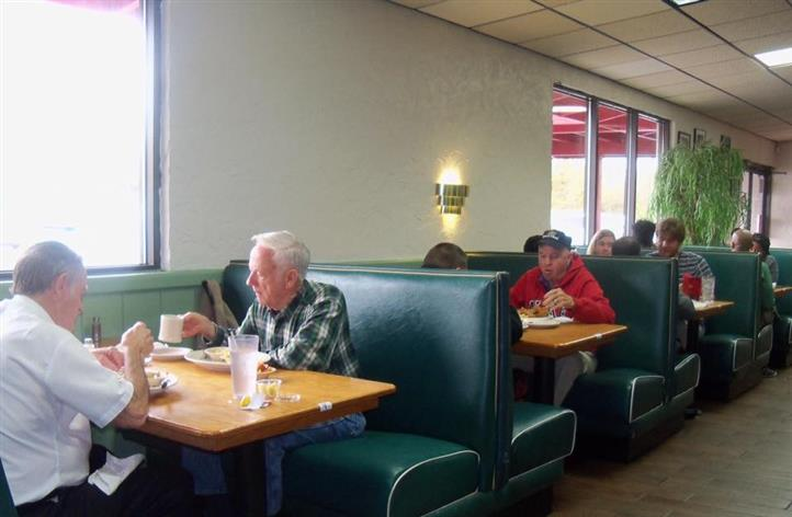 People sitting for a meal at the restaurant booths