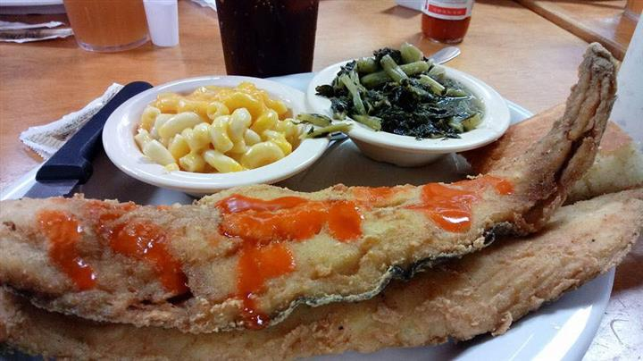 Fried fish filet with sides of mac and cheese and greens