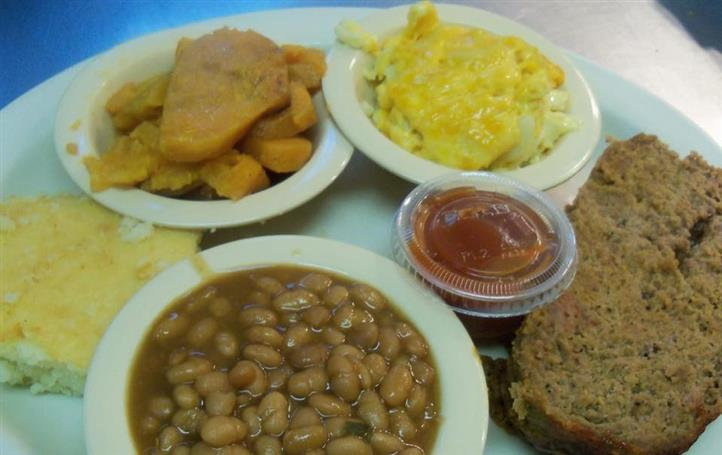 Tray of sides dishes suchs as baked beans, mac and cheese, sweet potatoes and a sauce with a bun