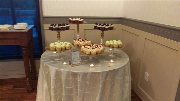 Round table with cake stands filled with  cupcakes